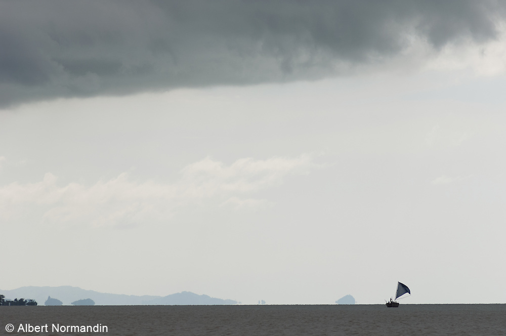Sailboat cruising on the Bay of Bengal with grey skies