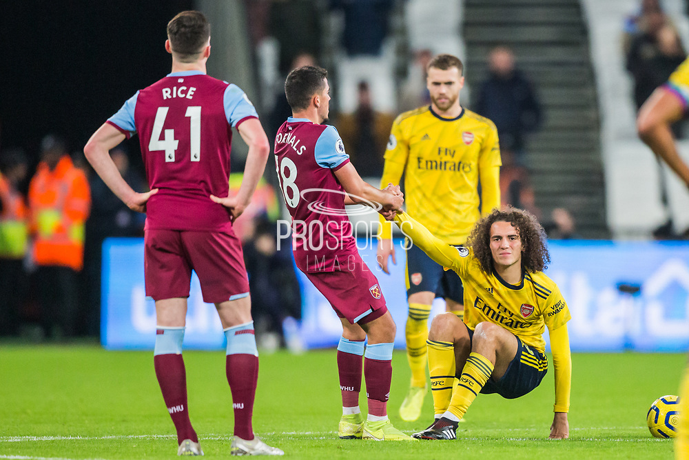 Matteo Guendouzi (Arsenal) on the ground and Pablo Fornals (West Ham) comes straight over to get him on his feet keen to get play underway again during the Premier League match between West Ham United and Arsenal at the London Stadium, London, England on 9 December 2019.
