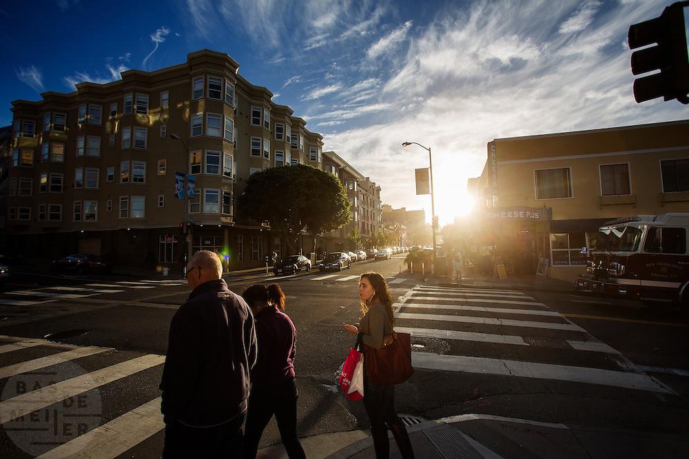 Voetgangers lopen in de avond op Polk Street. De Amerikaanse stad San Francisco aan de westkust is een van de grootste steden in Amerika en kenmerkt zich door de steile heuvels in de stad.<br /> <br /> Pedestrians in the evening at Polk Street. The US city of San Francisco on the west coast is one of the largest cities in America and is characterized by the steep hills in the city.