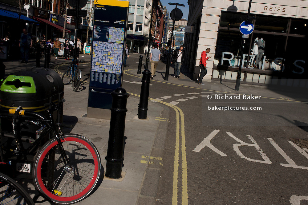 A red theme of a bicycle wheel and a young man wearing a red top, in a side street in London's west end.