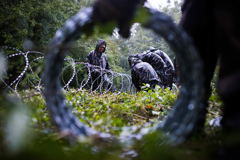 Hungarian soldiers construct a razorwire fence on the Croatian border on September 25, 2015 in Zakany, Hungary.