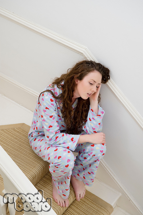 Young woman having headache while sitting on stairway