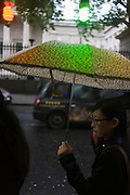 A woman walks beneath coloured lights during damp, gloomy weather in central London.
