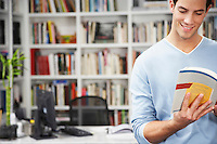 Young man reading book in front of bookshelf