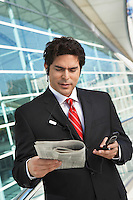 Businessman using mobile phone, reading newspaper outside office building
