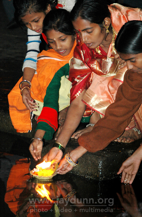 India, Maharashtra, Nasik, 2007. A Hindu family sends prayers into the Ramkund, which holds water from the Godavari River.