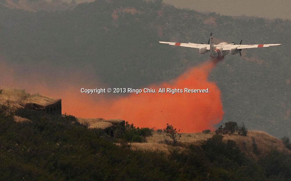 An air tanker drops fire retardant during a wildfire in Point Mugu, California, the United States, May 3, 2013. (Photo by Ringo Chiu/PHOTOFORMULA.com).