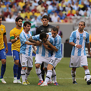 Ezequiel Lavezzi, Argentina, (centre) is restrained by team mates Lionel Messi and Hugo Campagnaro after being sent off during the Brazil V Argentina International Football Friendly match at MetLife Stadium, East Rutherford, New Jersey, USA. 9th June 2012. Photo Tim Clayton