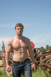 shirtless muscular man by a tractor