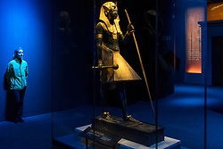 "© Licensed to London News Pictures. 01/11/2019. LONDON, UK. A staff member views ""Wooden Guardian Statue of the Ka of the King Wearing the Nemes Headcloth"".  Preview of ""Tutankhamun, Treasures of the Golden Pharoah"" at the Saatchi Gallery in Chelsea.  The exhibition celebrates the 100th year anniversary of the opening of Tutankhamun's tomb and displays 150 works in the largest collection of Tutankhamun's treasures ever to leave Egypt.  The show runs 2 November to 3 May 2020.  Photo credit: Stephen Chung/LNP"