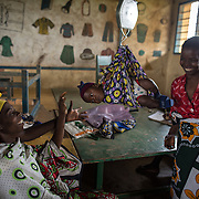 Mothers weigh their babies and have them vaccinated at an outreach health clinic set up in the tin-roofed classrooms at Ngamani Primary School. <br /> <br /> Data clerk Oscar Kai, came with his laptop and cooler of vaccines, on a motorcycle from the nearest medical center, a 20-minute drive along a bumpy dirt road. A distance that would take a mother carrying a child on foot, more than two hours. Oscar will input the names and dates of the children receiving the PCV 10 vaccine, as well as pentavalent, BCG, polio, yellow fever, measles, diphtheria, tetanus and hepatitis B immunizations. All of that information is then uploaded to portable hard-drives that are returned weekly to the study headquarters, where the database is updated.<br /> <br /> &quot;Because the database is digitized, it means it's far easier to keep our records fresh, even if children move and access health services in different locations,&quot; says Dr.Benjamin Tsofa, the Kenyan health ministry's chief liaison on the study. <br /> <br /> In January 2011, the Kenyan government with support from the GAVI Alliance, introduced a new vaccine, PCV-10, which targets 10 bacteria than can cause Invasive Pneumococcal Disease.The vaccine's impact is monitored through an electronic database, part of the GAVI funded PCV impact study, which maps the growing coverage of the new vaccine. Already, here in Kilifi, the incidence of the illness in children aged five has gone down by approximately two-thirds.