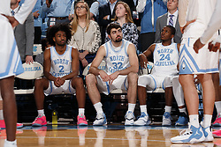 CHAPEL HILL, NC - FEBRUARY 05: Coby White #2, Luke Maye #32 and Kenny Williams #24 of the North Carolina Tar Heels sit on the bench during player introductions before a game against the North Carolina State Wolfpack on February 05, 2019 at the Dean Smith Center in Chapel Hill, North Carolina. North Carolina won 113-96. North Carolina wore retro uniforms to honor the 50th anniversary of the 1967-69 team. (Photo by Peyton Williams/UNC/Getty Images) *** Local Caption *** Coby White;Luke Maye;Kenny Williams