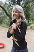 Black-tailed Deer<br /> Odocoileus hemionus<br /> Diane Nicholas, President of Kindred Spirits Fawn Rescue, carrying three-day-old orphaned fawn<br /> Kindred Spirits Fawn Rescue, Loomis, California