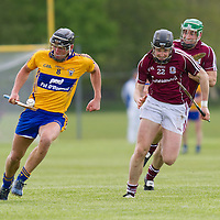 Clare's Shane Golden solo's the slíotar away from Galway's Kevin Hynes