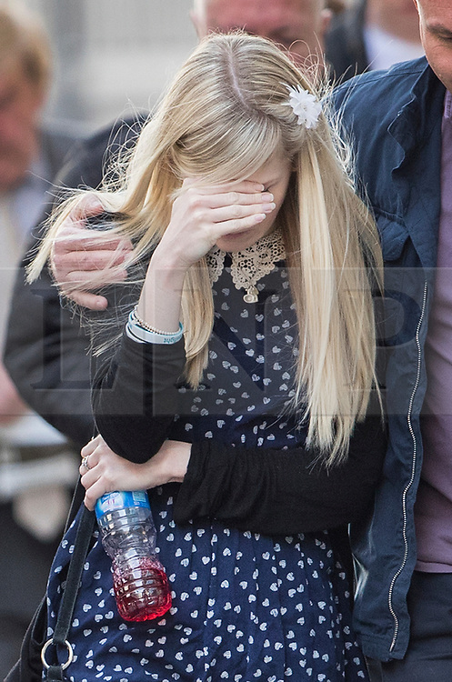 © Licensed to London News Pictures.11/04/2017.London, UK. A visible upset CONNIE YATES is comforted as she leaves The Royal Courts of Justice in London where a High Court judge has ruled that doctors can withdraw life-support treatment to their son, Charlie, who suffers from a rare genetic condition. Doctors at Great Ormond Street Hospital in London say eight-month-old Charlie should be left to die in dignity, but his parents have raised £1.2 million for specialist treatment in America. Photo credit: Peter Macdiarmid/LNP