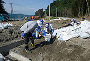 Unilever Japan staff  shovel mud to clear the drainage around the foundations of Dofukuin temple in Yagawahama, Ishinomaki, Miyagi Prefecture, Japan on 10 Sept. 2011. The entire area, including the temple, was flattened during the March 11 tsunami and around 35 Unilever and 4 BCCJ staff volunteered to do clean-up work. Photographer: ROBERT GILHOOLY