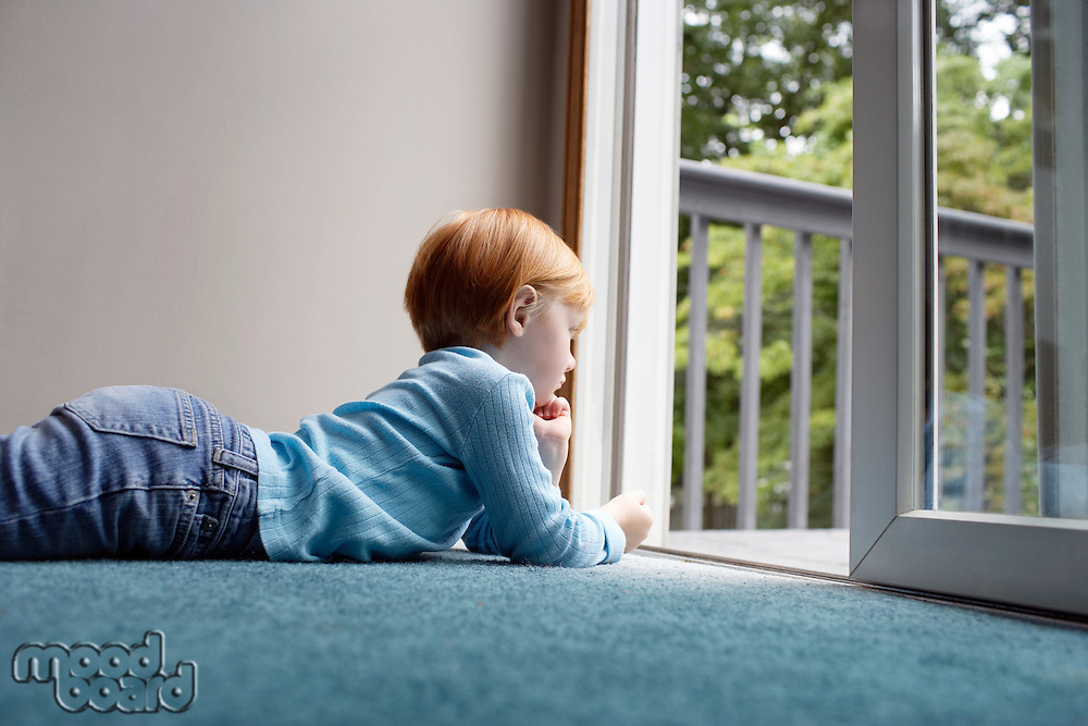 Young girl (5-6) lying on carpet looking through balcony door