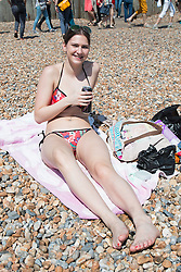 © Licensed to London News Pictures. 08/05/2016. Brighton, UK. 18 years old CHLOE from London on the beach as thousands of people take to the beach in Brighton to sunbathe as temperatures reach 22C down the South Coast. Photo credit: Hugo Michiels/LNP