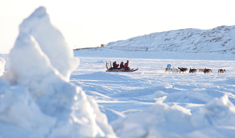 Canada's Finance Minister Jim Flaherty rides in a dogsled across a frozen Frobisher Bay off Iqaluit, Nunavut, Canada, February 5, 2010 as Canada plays host to the G7 Finance Ministers in the northern community. <br /> AFP/GEOFF ROBINS/STR