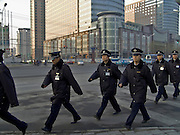 group of police officers marching through town China Beijing