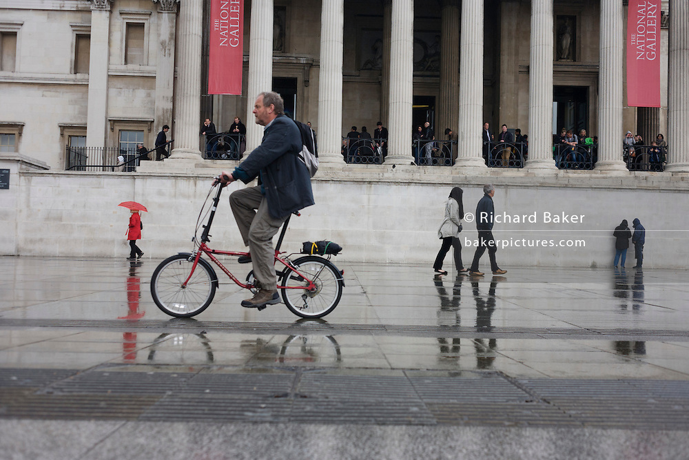 People and cyclist pass-by on the pedestrian pavement in Trafalgar Square in central London.