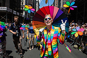 New York, NY - 30 June 2019. The New York City Heritage of Pride March filled Fifth Avenue for hours with participants from the LGBTQ community and it's supporters. A man under a rainbow umbrella wears a rainbow suit.