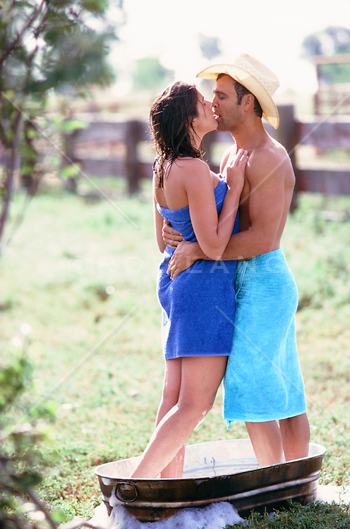 cowboy and a woman kissing while standing in an outdoor bathtub on a ranch in New Mexico