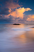 An already tall cumulonimbus storm cloud continues to build over the Pacific Ocean near Sayulita, Mexico at sunrise.