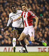 Emmanuel Adebayor of Tottenham Hotspur closes down Chris Basham of Sheffield United during the Capital One Cup Semi-Final 1st Leg match between Tottenham Hotspur and Sheffield Utd at White Hart Lane, London, England on 21 January 2015. Photo by David Horn.