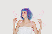 Beautiful young woman dressed as angel with dyed hair looking up against gray background