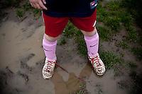 Children play soccer on a very muddy field in Portland, Oregon.<br /> Girls soccer.  pink