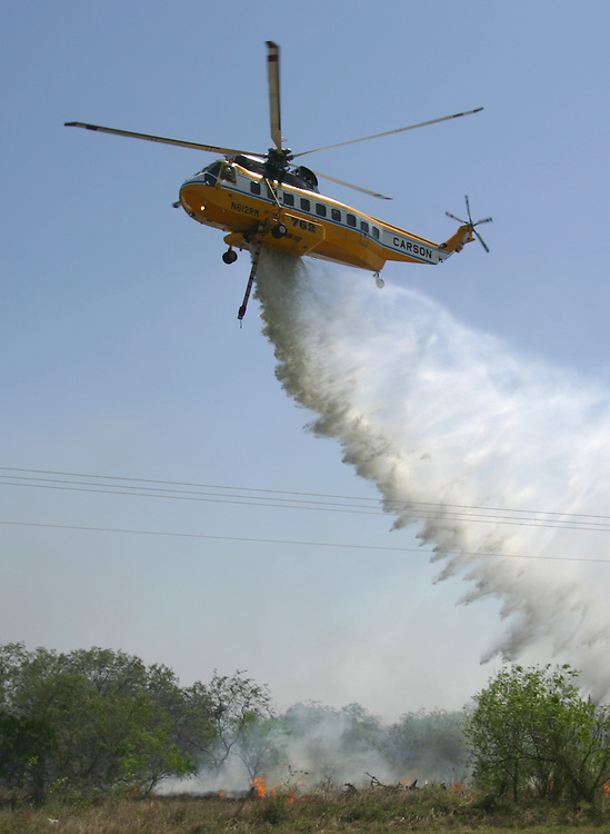 Encino, TX - 19 Mar 2008 -A Sikorsky S-61N helitanker operated by Carson Helicopters makes a water drop to control a brush fire in Encino on Wednesday afternoon.  Photo by Alex Jones / ajones@themonitor.com