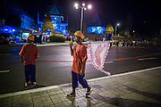"""01 FEBRUARY 2013 - PHNOM PENH, CAMBODIA: A participant in the funeral procession of former King Norodom Sihanouk walks along Sisowath Quay early in the morning of Feb 1, before Sihanouk's funeral procession left the palace. Norodom Sihanouk (31 October 1922- 15 October 2012) was the King of Cambodia from 1941 to 1955 and again from 1993 to 2004. He was the effective ruler of Cambodia from 1953 to 1970. After his second abdication in 2004, he was given the honorific of """"The King-Father of Cambodia."""" Sihanouk died in Beijing, China, where he was receiving medical care, on Oct. 15, 2012. His cremation is will be on Feb. 4, 2013. Over a million people are expected to attend the service.    PHOTO BY JACK KURTZ"""