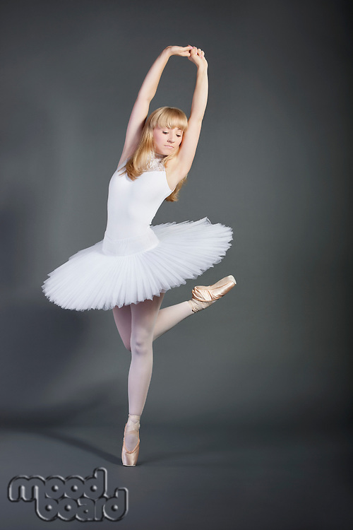 Young woman in white tutu performing ballet over grey background