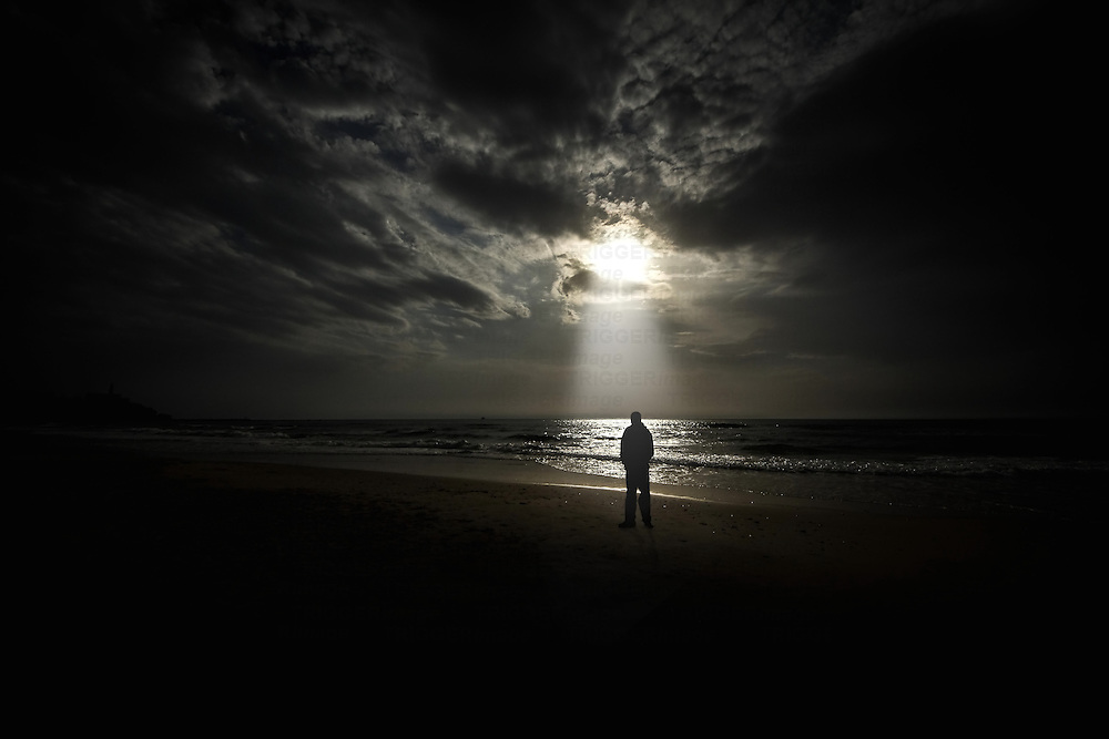 Conceptual beach scene with lone male figure and sunbeam