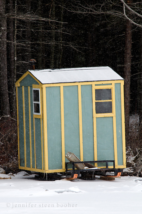 A green-and-yellow painted ice fishing hut on a sledge, ready to be pulled onto the frozen lake.