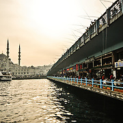 Hidayet Cami in Eminonu as seen from Galata Bridge in the late afternoon. Rows of fishermen