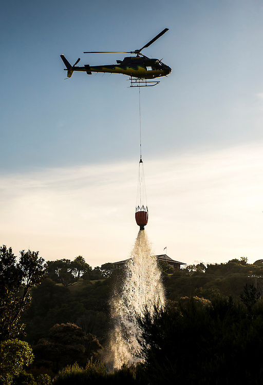 A helicopter douses hot spots from a scrub fire which threatened homes on Tutukaka Block Road, Northland, New Zealand. Wednesday December 30, 2015. Credit:SNPA / Malcolm Pullman