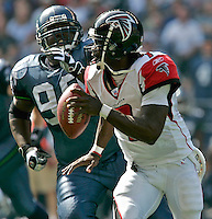Atlanta's QB #7 Michael Vick runs from Seattle's Rocky Bernard in the home opener at Qwest Field in Seattle, Washington on Sunday Sept. 18, 2005(Kevin P. Casey/Wireimage.com)