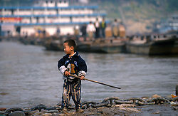 CHNA SICHUAN PROVINCE CHONGQUING MAY99 - A young Chinese boy stands at the shore of the Yangtse river where it merges with the Jailing river at Chongquing. Seven large cities, including Chongquing, and thousands of villages will be submerged once the water level rises after the completion of the controversial Three Gorges Dam project further downriver. The flooding of areas reaching back more than 550Km upriver will require the evacuation and resettlement of more than 10 million people.  jre/Photo by Jiri Rezac