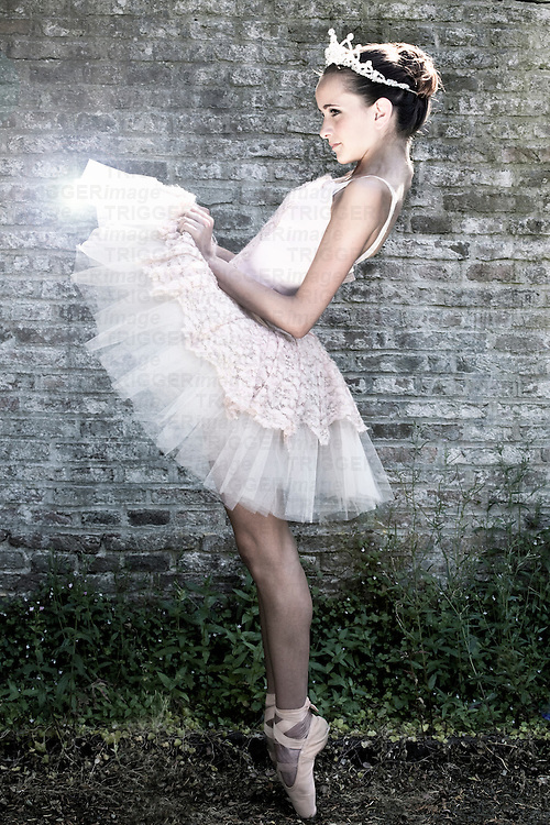 Female youth wearing ballet tutu standing on point lifting lace frills