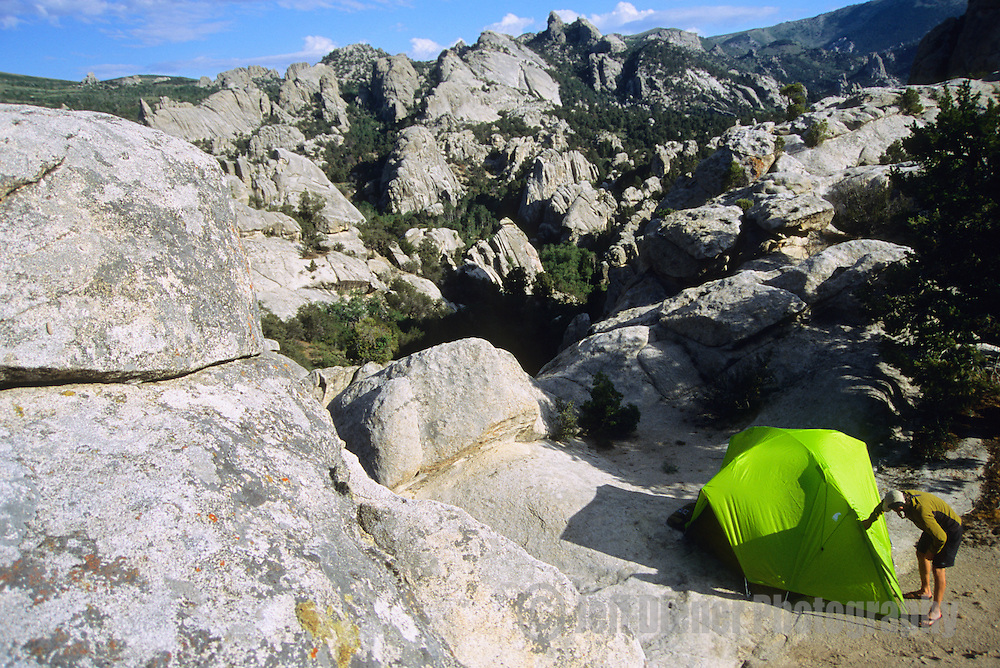 A young man zips his tent while camping in the City of Rocks National Reserve, Idaho.