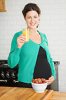 Pregnant woman drinking fruit juice in kitchen portrait