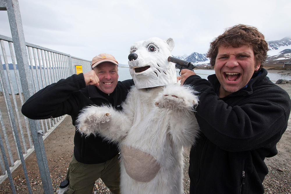 Norway, Svalbard, Ny Ålesund, Photographers Paul  Souders and Steve Kazlowski clowning with costumed polar bear at dock in small arctic research station