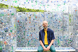 "© Licensed to London News Pictures. 24/05/2018. LONDON, UK. Architect Nick Wood poses at the unveiling of an art installation called ""Space of Waste"", in ZSL London Zoo.  The artwork, designed by Nick Wood, comprises a building made of 15,000 discarded single-use bottles collected from London and its waterways and is part of ZSL's #OneLess campaign, aiming to protect the world's oceans by encouraging people to stop using single-use plastic bottles.  Photo credit: Stephen Chung/LNP"