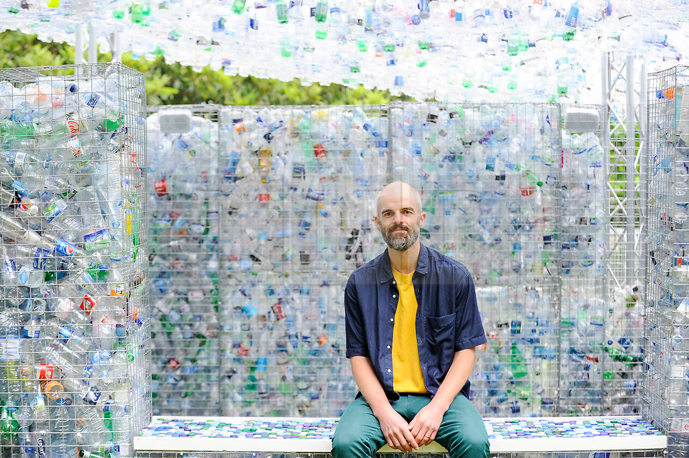"""© Licensed to London News Pictures. 24/05/2018. LONDON, UK. Architect Nick Wood poses at the unveiling of an art installation called """"Space of Waste"""", in ZSL London Zoo.  The artwork, designed by Nick Wood, comprises a building made of 15,000 discarded single-use bottles collected from London and its waterways and is part of ZSL's #OneLess campaign, aiming to protect the world's oceans by encouraging people to stop using single-use plastic bottles.  Photo credit: Stephen Chung/LNP"""