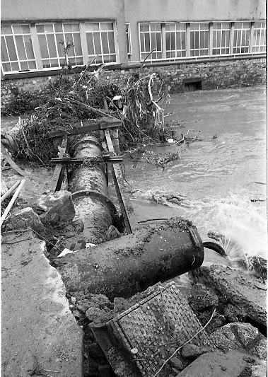"""Flooding at the Dodder..1986..26.08.1986..08.26.1986..28th August 1986..As a result of Hurricane Charly (Charlie) heavy overnight rainfall was the cause of severe flooding in the Donnybrook/Ballsbridge areas of Dublin. In a period of just 12 hours it was stated that 8 inches of rain had fallen. The Dodder,long regarded as a """"Flashy"""" river, burst its banks and caused great hardship to families in the 300 or so homes which were flooded. Council workers and the Fire Brigades did their best to try and alleviate some of the problems by removing debris and pumping out some of the homes affected..Note: """"Flashy"""" is a term given to a river which is prone to flooding as a result of heavy or sustained rainfall...Image of the watermain crossing the Dodder covered with debris as a result of the deluge."""