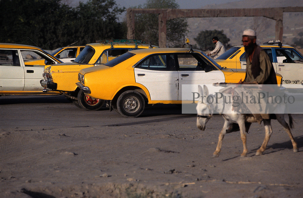 Kabul, 26 July 2005. Yellow & White Taxi Cabs park on a main road waiting for customers. A man use the traditional donkey for moving around.