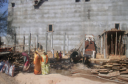 Large concrete building being constructed by female workers,