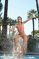 Father throwing daughter in swimming pool
